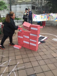 Bread client leader Zonia Godinez symbolically breaking down barriers to stability, as part of an action with Fair Budget Coalition outside the John A. Wilson Building